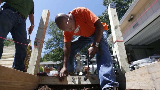 Walter Hall, a volunteer from Home Depot, nails in a bracket as he helps build a wheelchair ramp at a veterans home as part of the United Way's Day of Caring in 2015.