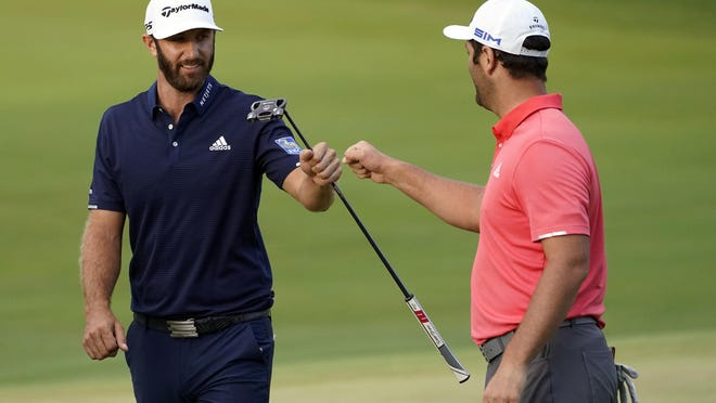 Jon Rahm, right, is congratulated by Dustin Johnson on the first playoff hole at the Olympia Fields Country Club on Sunday.