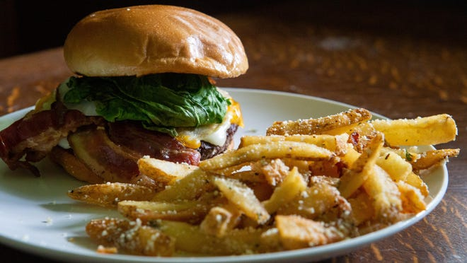 The Johnny Wilson burger comes with Swiss, cheddar and bacon with lettuce, pickles and onion on the side for $9.99 with one side. Garlic Parmesan fries with truffle oil can be added for $1.99.