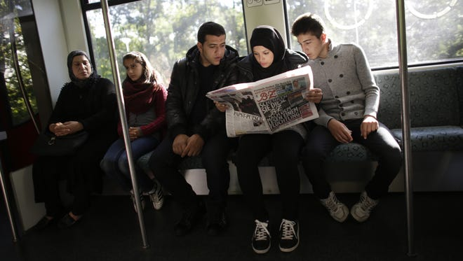 Syrian refugees Reem Habashieh, second from right, and her brothers, Mohammed Habashieh, left, and Yaman Habashieh read a local newspaper on a train with their mother, Khawla Kareem, far left, and sister, Raghad Habashieh. The family arrived in Berlin in September, five of the 37,000 who have flooded into Germany this month seeking a new life.