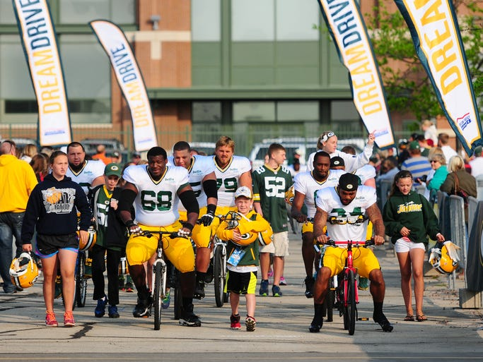 Green Bay Packers players ride bikes to training camp practice at Ray Nitschke Field on Monday, July 28, 2014.
