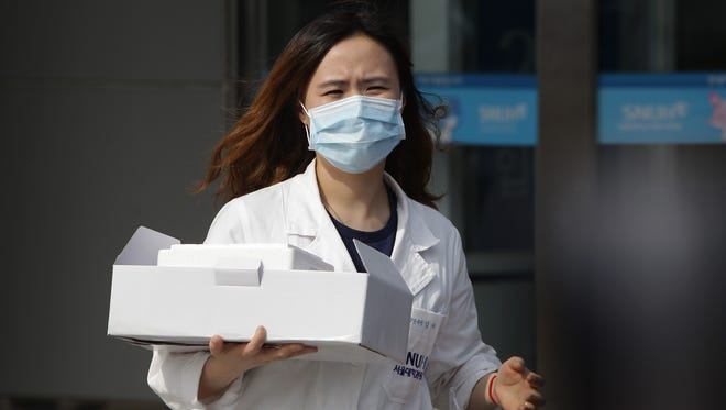 A hospital worker takes supplies to a quarantine tent for people possibly infected with the MERS virus at Seoul National University Hospital on June 2, 2015, in Seoul. The Ministry of Health and Welfare of South Korea confirmed two deaths from Middle East Respiratory Syndrome (MERS) on June 2, 2015. It reported six new cases of MERS, raising the number of confirmed local patients to 25. The first case was confirmed May 20.