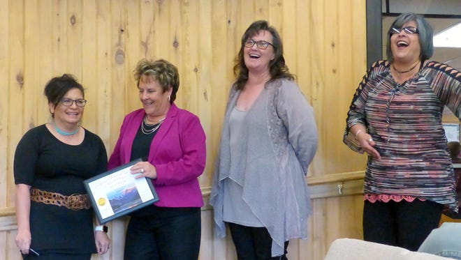 Village Finance Director Judy Starkovich, at left, receives the award for her department from Village Manager Debi Lee. Enjoying the moment are department staff members from left, Robin Parks and Karen Gutierrez.