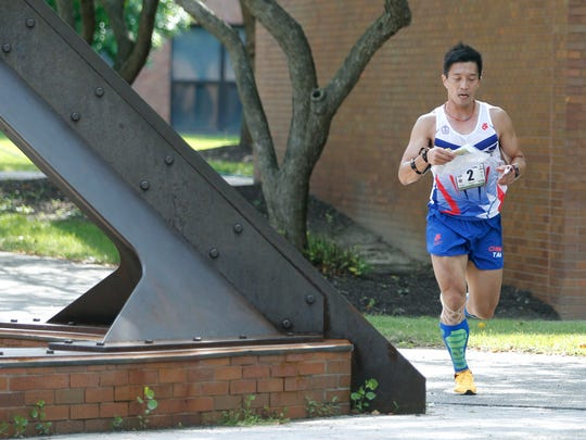 Mao-Ying Huang of Chinese Taipei runs while checking the map during the sprint two kilometer race of the World Deaf Orienteering Championship at RIT.