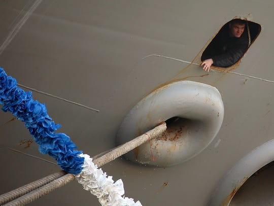 A sailor looks out one of the portholes as the USS