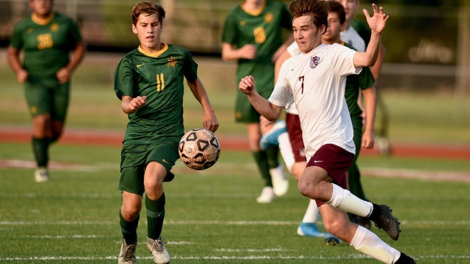 Salina Central's Logan Johnson (7) and Salina South's Carson Crow (11) battle for the ball Tuesday night at Salina Stadium. South got a late goal to win, 2-1.
