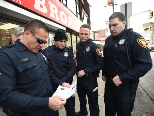 Three Paterson Police Officers (2nd from L) Ferdi Abedinoski, Edward J. Akins and Salvador Brancato who graduated from Police Academy last week, look toward their Supervisor Senior Officer Nalson Paez as he checks a permit from a vendor during their patrols for the first time in commercial shopping districts in downtown Paterson on 12/19/17.