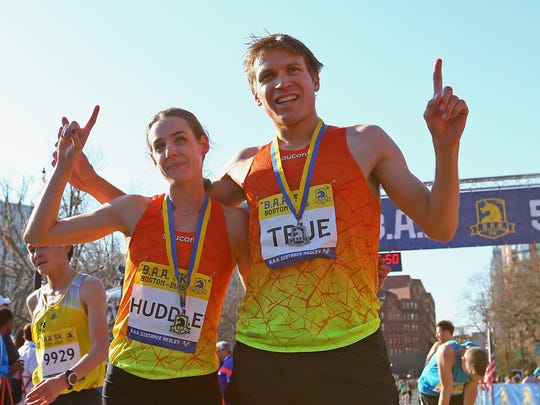 Molly Huddle and Ben True, both of the United States, celebrate after their wins Saturday at the BAA 5K in Boston.
