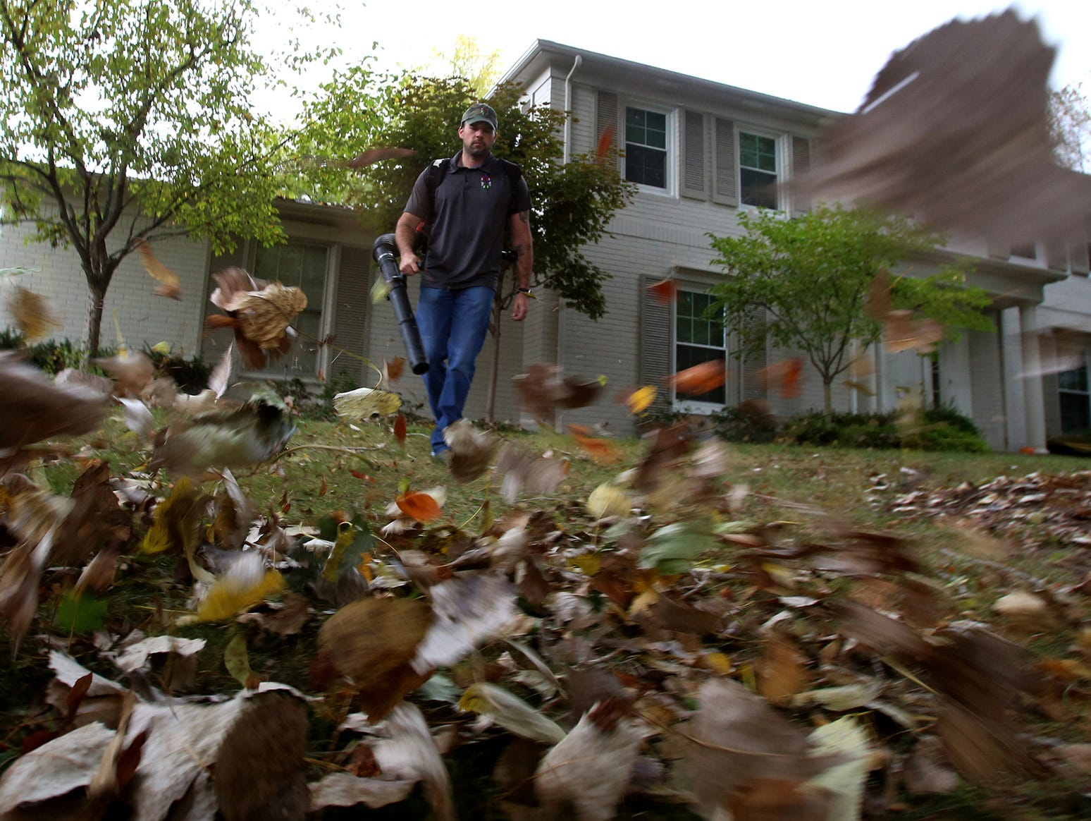 Stars and Stripes Lawn Care co-owner Chris Kamyszek uses a leaf blower to clean up a client's yard in Bloomfield Hills, Mich., on Friday, Oct. 9 2015. Kamyszek thinks that the use of an app like the one from Plowz & Mowz, will help shape the industry