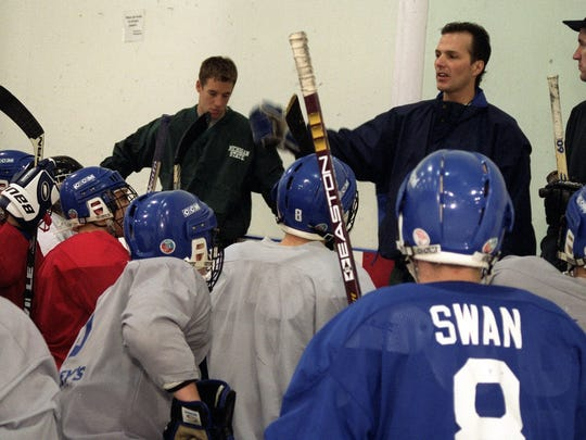 Coaches Jon Cooper, left, and Pat Murray talk to the Lansing Catholic Central varsity hockey during practice at The Summit.