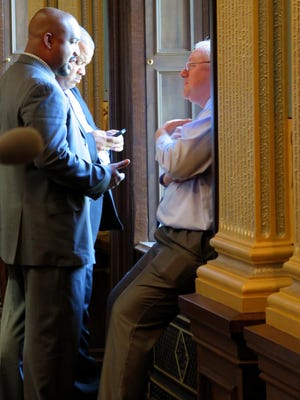 Sen. Bert Johnson, D-Highland Park, left, and Sen. Rick Jones, R-Grand Ledge, right, talk in the Michigan Senate chamber, Wednesday, July 1, 2015, in Lansing, Mich. A Michigan legislative resolution recognizing a holiday that celebrates the end of slavery is on hold because Republican leaders are uncomfortable with the language. (AP Photo/David Eggert)