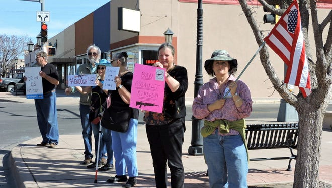 About a dozen demonstrators gathered at Leyendecker Plaza on Saturday morning to stand against gun violence.
