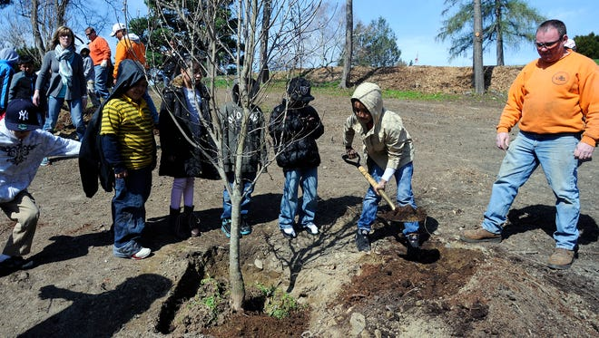 Warring Magnet Academy of Science and Technology second-grader Kadofi Abbott, center, right, shovels during a tree planting ceremony at College Hill Park on Friday in the City of Poughkeepsie. At right is Cal McQuade of the City of Poughkeepsie Department of Public Works Tree Department.