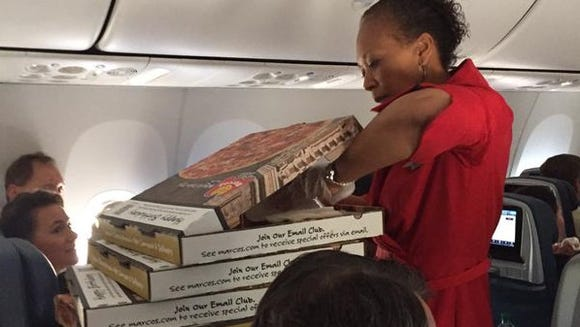 A Delta flight attendant passes out passengers to delayed