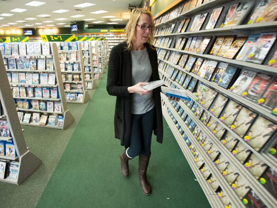 Kristin Acord, manager, restocks shelves at the Family Video, at the corner of Emerson and 10th.