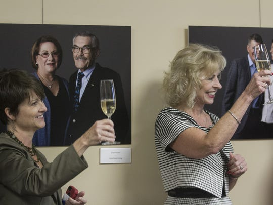 Carolyn Rogers, left, and Robbie Roepstorff raise their glasses to toast the philanthropists featured in the latest photography exhibit at the Southwest Florida Community Foundation. The photographs were made by local photographer Brian Tietz.