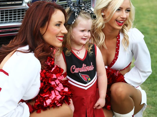Lillian Garsha, age 2 1/2 from Buckeye, Ariz. poses with the Arizona Cardinals cheerleaders at the draft party on Thursday, April. 27, 2017 on the great lawn at University of Phoenix in Glendale, Ariz.