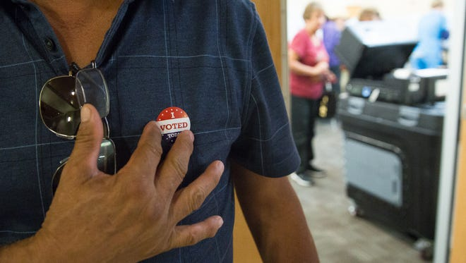 """Marco Torres, sticks a """"I voted"""" sticker to his shirt after leaving the polling station at the Doña Ana County Government Center, Thursday October 20, 2016."""