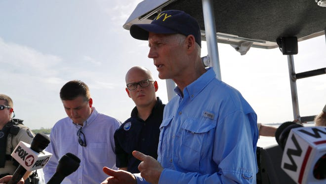 Gov. Rick Scott answers questions after touring the algae blooms in the Caloosahatchee River on Monday, July 9, 2018.