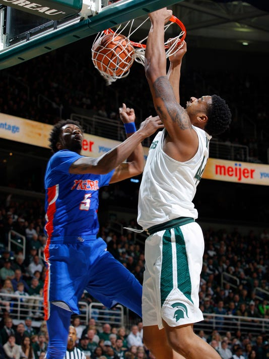 Michigan State's Nick Ward, right, dunks against Savannah State's Javaris Jenkins (5) during the first half of an NCAA college basketball game, Sunday, Dec. 31, 2017, in East Lansing, Mich. (AP Photo/Al Goldis)