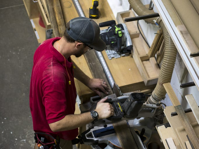 Austin Bell cuts wood for a church pulpit, June 27,