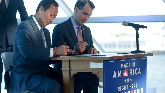 Foxconn Chairman Terry Gou (left) and Gov. Scott Walker sign a memorandum of understanding regarding Foxconn's plan to build a $10 billion factory in Wisconsin.