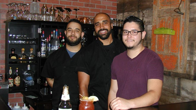 Left of Center's staff include, from left, head chef Arthur Grijalva, executive chef Kyran Wiley, and Andrew Grijalva, mixologist and baker. In the foreground is Modelo beer used in making the signature drink, Michelada