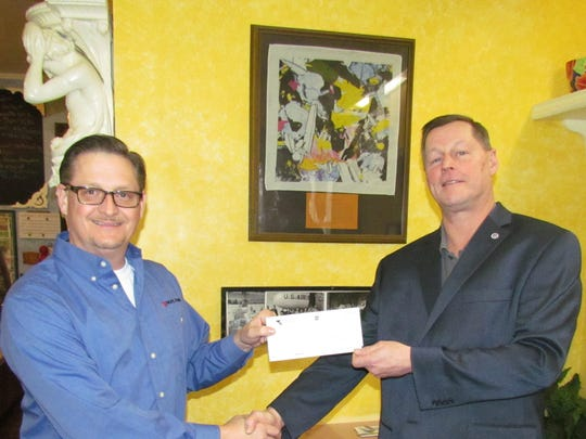 Pacific Power Foundation's Alan Meyer awards a $3,000 check for a grant to JPL Museum caretaker James Loftus at the Gardner House in Stayton.