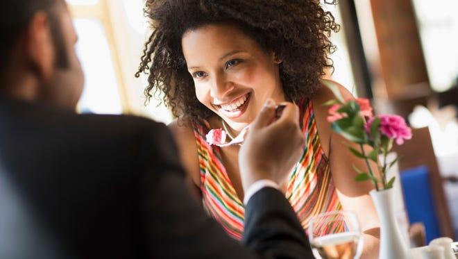 Man holding a bite of dessert for a girlfriend.