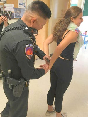 Santa Clara corporal Jaime Serrano arrests Brenda Hernandez during a fundraiser for the WNMU Chemical Dependency and Criminal Jusice Club on Thursday morning.