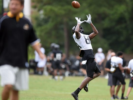 Southern Miss wide receiver Isaiah Jones reaches the ball during a pass routine during the fall football camp on Wednesday.
