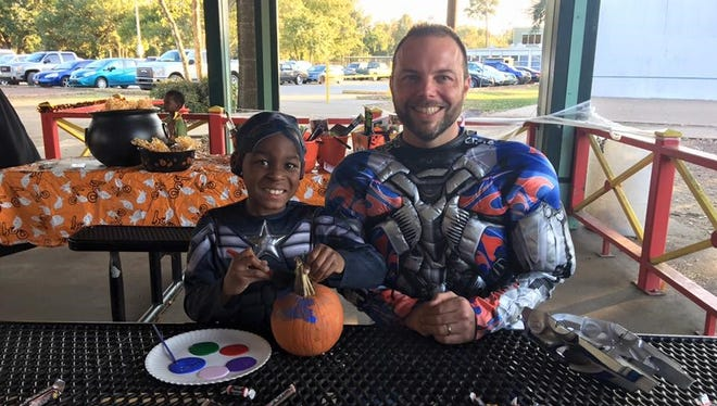 Aiden Coleman, 7, spends time with his mentor, Jason Redmon, at the Big Brothers Big Sisters of Acadiana Halloween party at Girard Park. Aiden is dressed as Captain America, and Redmon is dressed as Optimus Prime.