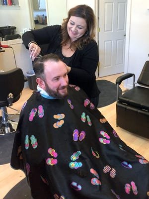 Stephanie Sanchez, owner of A New Direction cuts Silver City resident Brad Wood's hair Thursday afternoon.