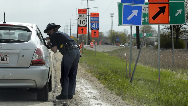 Wisconsin State Patrol Sgt. Tim McGrath talks to a driver about excessive speed during a stop on State 441/U.S. 10 in Menasha in 2017. Wm. Glasheen/USA TODAY NETWORK-Wisconsin.