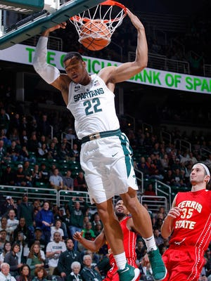 Michigan State's Miles Bridges (22) dunks on the first play after the tip against Ferris State's Zach Hankins (35) Thursday, Oct. 26, 2017, in East Lansing, Mich.
