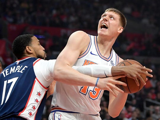 New York Knicks forward Henry Ellenson, right, tries to shoot as Los Angeles Clippers guard Garrett Temple defends during the first half of an NBA basketball game Sunday, March 3, 2019, in Los Angeles. (AP Photo/Mark J. Terrill)