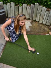 Kena Yoke tries out her unconventional putting style at the Collier County Honor Flight fundraising event.