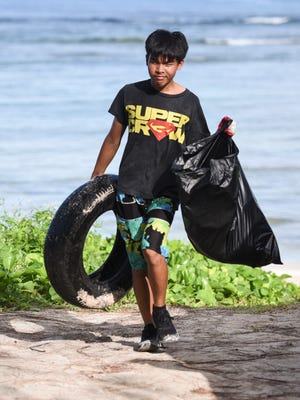 In this Sept. 16 file photo, Zaine Benavente carries a bag of trash and an old rubber tire collected during the 23rd Annual Guam International Coastal Cleanup 2017 at Tanguisson Beach.