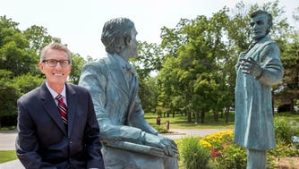 "Carthage College's Bill Abt sits by ""A Learning Moment,"" the bronze sculpture featuring Abraham Lincoln and John Hay."