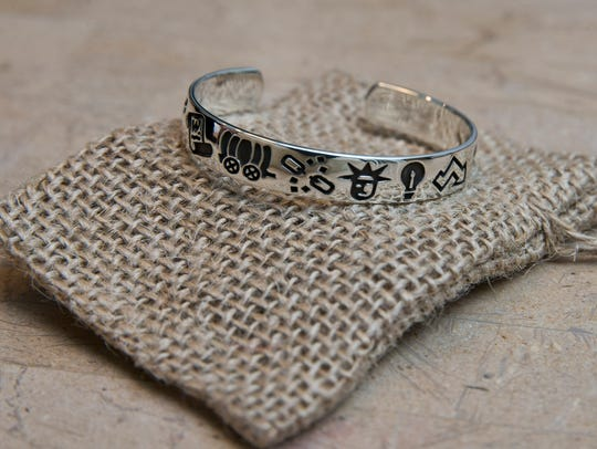 The icons on this LLPH bracelet represent various periods