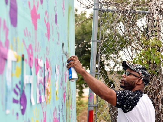 Jafar Cox of York adds his own touch during the Penn Street Art Bridge Launch Party on the north side of the North Penn Street bridge near Smyser Street Saturday, July 29, 2017, in York. UpCollective York and York Time Bank collaborated to turn the bridge, which has long been a target of graffiti, into a public art space that anyone can transform with paint.