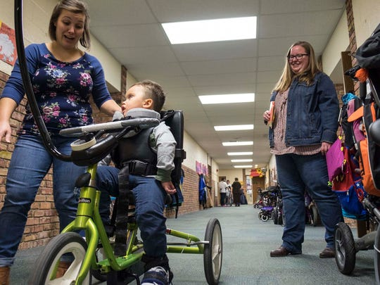 Ben's mother Jamie Welser, right, watches as Woodlands Developmental Center teacher Ashley Erard, right, leads Ben Welser, 3, down the hallway of the school on a tricycle designed for special needs kids Nov. 7.