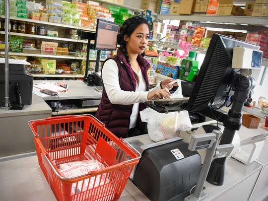 Linh Ngyuen helps a customer check out at Viet Tien International Market and Deli Monday, March 19, in Waite Park.