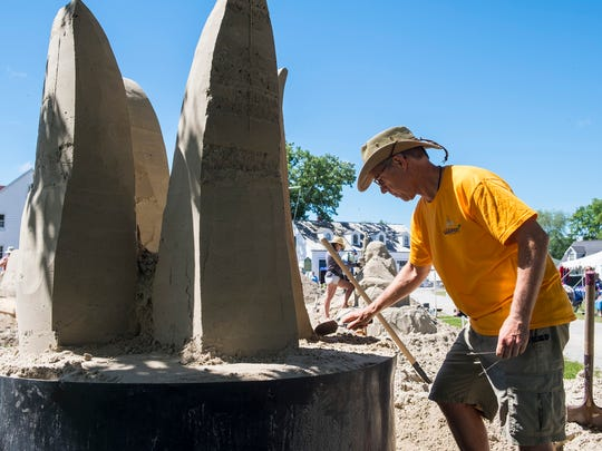 Todd Pangborn works on his abstract sculpture during the first day of Blue Water Sandfest Friday, July 6, 2018, at the Fort Gratiot Lighthouse. Pangborn's sculpture is about the lost art of automotive design, and will be ideas flowing down into a hand holding pencil that turns into cars and antique hood ornaments.