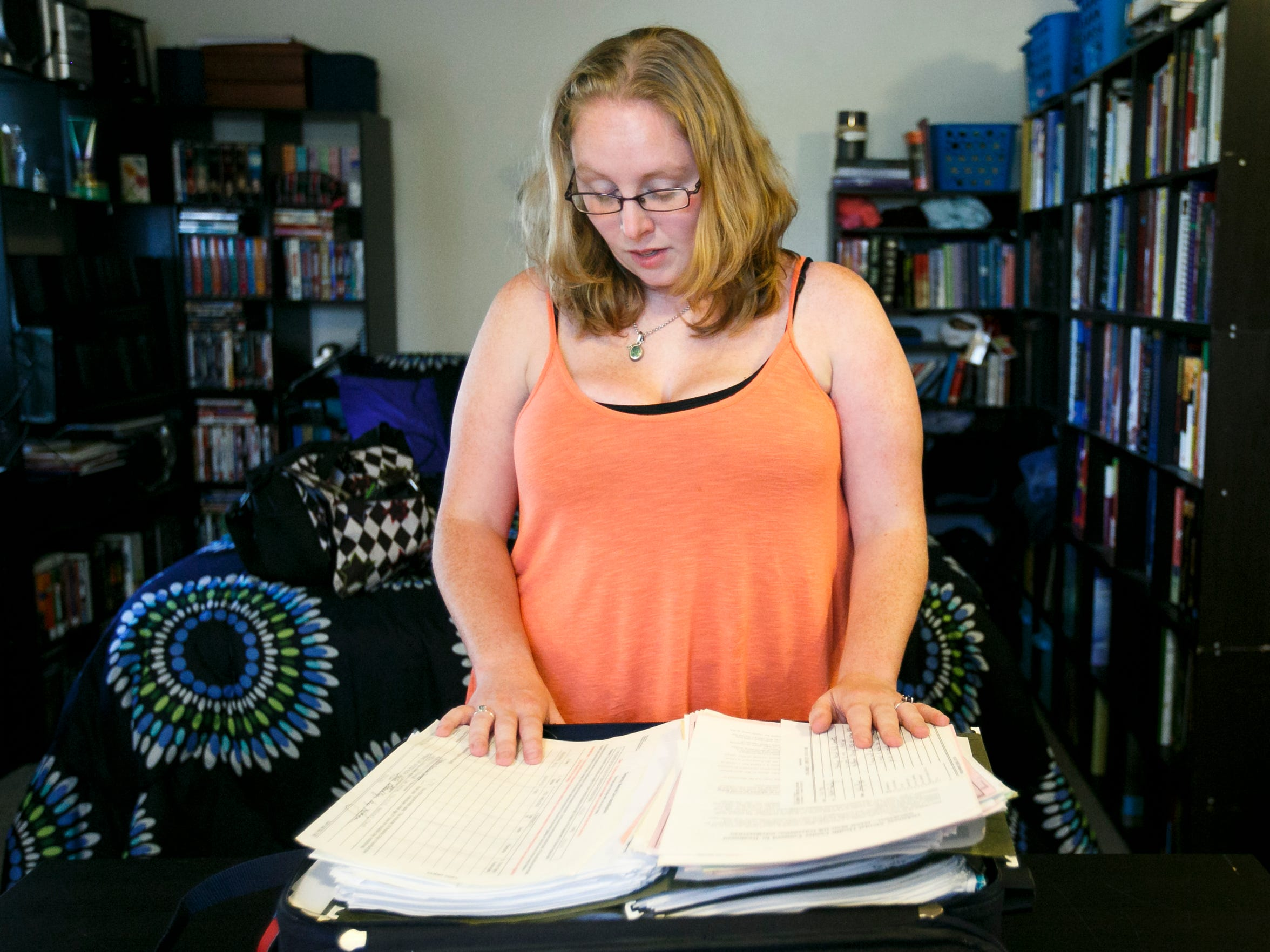 Mia Storm looks at a suitcase full of her medical records and reports from the 14 years she spent in the foster care system. She was shuffled through nearly 20 foster homes and heavily medicated in the years she spent under state supervision. Now 32, she is working to gain her independence and raise her daughter Lily.