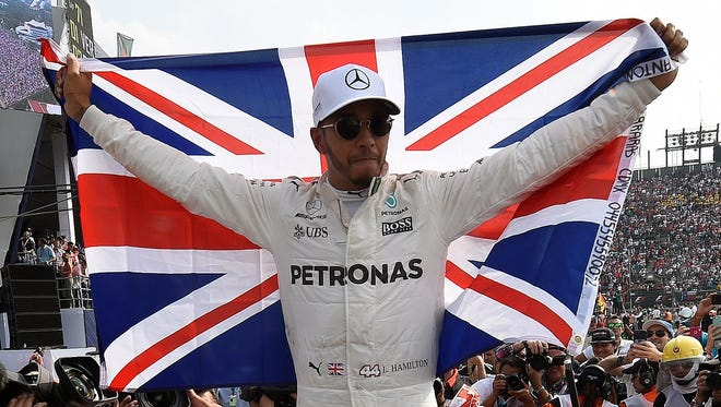 Lewis Hamilton celebrates after winning his fourth Formula One championship with a ninth-place finish at Sunday's Mexican Grand Prix.