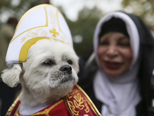 Michelle Guillen and her shih tzu Jojo wear a Pope and a nun costume as they participate in the annual Tompkins Square Halloween Dog Parade in New York on Saturday, Oct. 24, 2015.