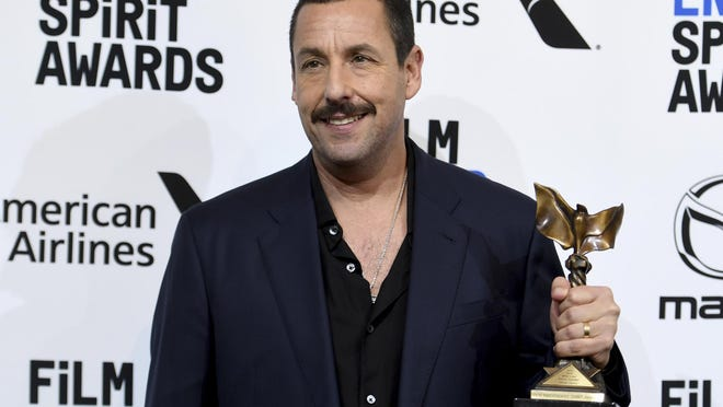 """Adam Sandler poses in the press room with the award for best male lead for """"Uncut Gems at the 35th Film Independent Spirit Awards on Saturday, Feb. 8, 2020, in Santa Monica, Calif."""