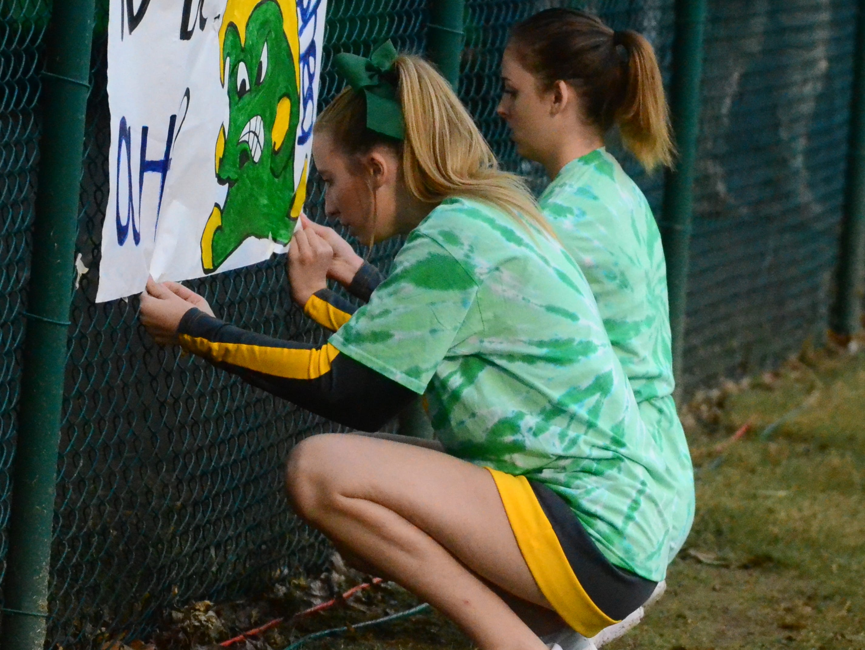 Gallatin High School cheerleaders attach a sign to the fence prior to their game at Gallatin on Friday, September 30, 2016.