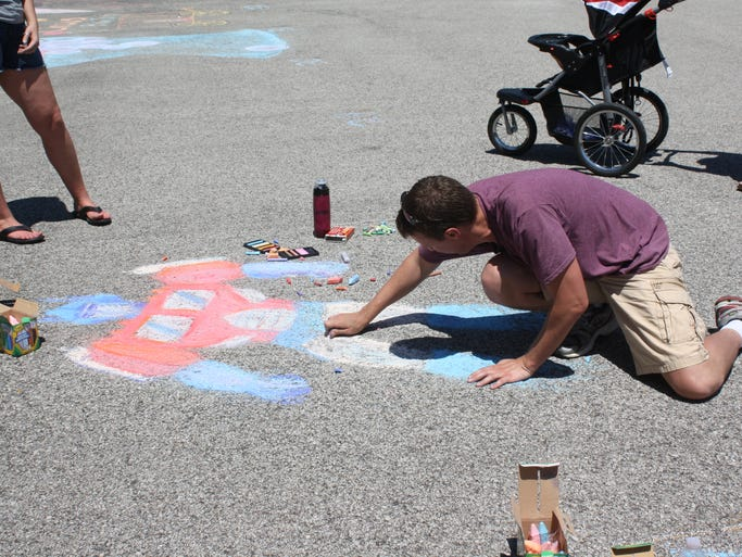 Nick Schueren of Jeffersonville puts the finishing touches on his chalk drawing of  Transformers character Optimus Prime during the Clarksville Chalk Walk Festival at the town hall on Saturday.  (By Jenna Esarey, special to The Courier-Journal)  May 31, 2014.